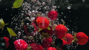 I lamponi freschi con i mirtilli e le foglie di menta fresca cadono su un fondo nero nell'acqua, spruzzante sul nero archivi video