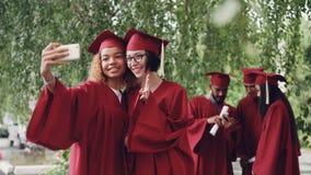 I laureati abbastanza femminili stanno prendendo il selfie con il rotolo del diploma facendo uso dello smartphone, giovani donne  video d archivio