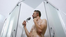 I lavaggi allegri e attivi dell'uomo nella doccia e divertente canta e ballo video d archivio