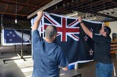 I lavoratori appendono una stampa della bandiera nazionale della Nuova Zelanda Fotografia Stock