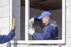 I lavoratori asiatici installano le finestre alla casa fotografia stock
