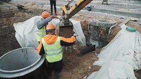 I lavoratori in caschi conduce l'escavatore che scarica la sabbia sul tubo di plastica nella fossa stock footage