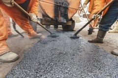 I lavoratori che riparano la strada con le pale riempiono la riparazione della strada privata dell'asfalto Immagini Stock