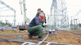 I lavoratori collegano l'attrezzatura con i tubi lunghi al sito stock footage