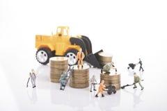 i lavoratori con il mucchio coniano i soldi e l'industria dell'edilizia di affari Fotografia Stock