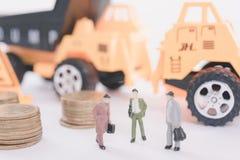 i lavoratori con il mucchio coniano i soldi e l'industria dell'edilizia di affari Fotografie Stock Libere da Diritti