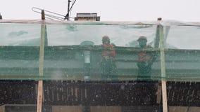 I lavoratori dei costruttori stanno sull'armatura della costruzione e gettano la neve dal tetto stock footage