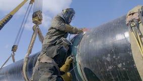 I lavoratori dell'industria che saldano la condotta d'acciaio convogliano utilizzando la torcia del metallo nel giorno di inverno archivi video