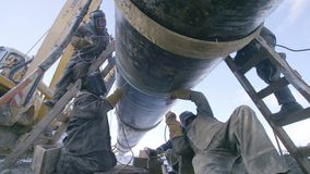I lavoratori dell'industria che saldano la condotta d'acciaio convogliano utilizzando la torcia del metallo nel giorno di inverno video d archivio