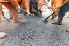 I lavoratori della strada hanno posto l'asfalto, riparante la strada Immagine Stock