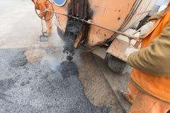 I lavoratori della strada hanno posto l'asfalto, riparante la strada Immagine Stock Libera da Diritti