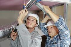 I lavoratori dello stipendio hanno fissato il profilo del soffitto in nuovo piano Fotografia Stock