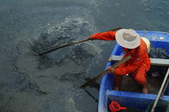 I lavoratori di risanamento puliscono i rifiuti nel fiume Immagine Stock