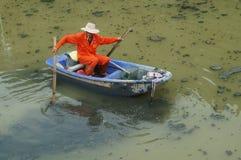 I lavoratori di risanamento puliscono i rifiuti nel fiume Fotografia Stock