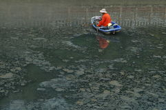 I lavoratori di risanamento puliscono i rifiuti nel fiume Fotografie Stock
