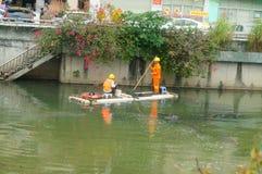 I lavoratori di risanamento stanno pulendo l'immondizia del fiume immagini stock libere da diritti