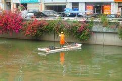 I lavoratori di risanamento stanno pulendo l'immondizia del fiume fotografie stock