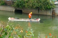 I lavoratori di risanamento stanno pulendo l'immondizia del fiume fotografia stock