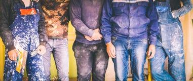 I lavoratori ed i costruttori ed il caporeparto sono mentre il gruppo con l'uniforme sporca sta restando in appartamento che è in fotografie stock libere da diritti
