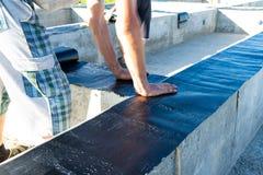 I lavoratori effettuano l'impermeabilizzazione del fondamento per la costruzione di una casa di legno fotografie stock libere da diritti