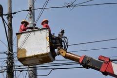 I lavoratori elettrotecnici su Telehandler con il secchio che installa i cavi di alta tensione sulla parte di sotto concreta alta Immagine Stock Libera da Diritti