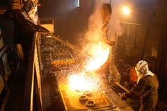 I lavoratori funziona nella pianta metallurgica Ferro di fusione nella fonderia Metallo liquido nella fabbrica, nel ferro di fusi Immagine Stock