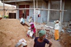 I lavoratori indiani nella costruzione di calcestruzzo alloggia vicino al mucchio della sabbia Immagini Stock Libere da Diritti