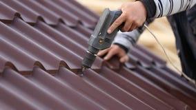 I lavoratori installano il tetto del metallo