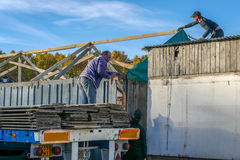 I lavoratori installano le case di legno Fotografia Stock