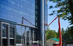I lavoratori lavano le finestre in una costruzione di vetro nella citt? immagini stock libere da diritti