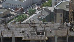 I lavoratori mette il rinforzo sul cantiere non finito di edificio residenziale video d archivio