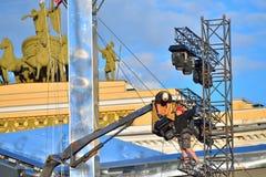 I lavoratori montano un palo di illuminazione al color scarlatto delle vele al palazzo immagine stock
