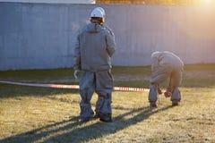 I lavoratori nella serie chimica della protezione stanno imbarcando sulla zona contaminata immagini stock