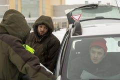 I lavoratori parlano alla porta aperta dell'automobile immagine stock