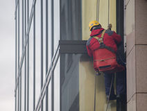 I lavoratori puliscono la facciata della costruzione Fotografia Stock