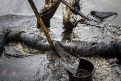 I lavoratori rimuovono il petrolio greggio da una spiaggia Fotografia Stock