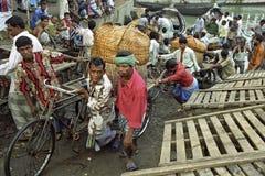 I lavoratori scaricano le barche in porto occupato Dacca Fotografia Stock