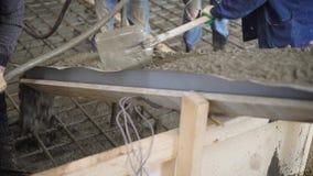 I lavoratori sono stenditura della miscela di calcestruzzo dentro sopra l'ingabbiatura per la fabbricazione del pavimento della c archivi video