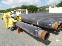 I lavoratori stanno controllando i tubi di olio prima della presa nell'operazione nel mare fotografia stock
