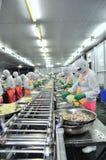 I lavoratori stanno lavorando la persona dura una linea di produzione in una fabbrica dei frutti di mare nella città di Ho Chi Mi Fotografie Stock