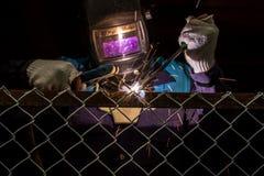 I lavoratori stanno saldando la maglia d'acciaio nell'area di lavoro Fotografie Stock Libere da Diritti