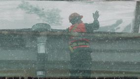 I lavoratori stanno sull'armatura coperta di rete verde e gettano la neve dal tetto archivi video