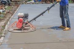 I lavoratori stanno utilizzando le levigatrici concrete per cemento dopo il versamento del calcestruzzo pronto per l'uso fotografia stock