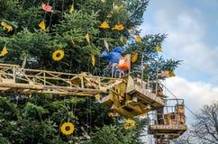I lavoratori in un canestro all'altezza del rubinetto a macchina si agghindano l'albero di Natale delle decorazioni e dei giocatt Fotografia Stock Libera da Diritti