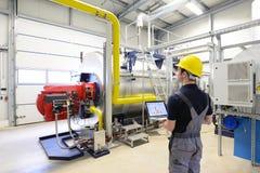 I lavoratori in un impianto industriale controllano i sistemi con tecnico moderno immagini stock