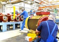 I lavoratori in una fabbrica montano i motori elettrici immagine stock libera da diritti
