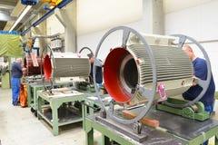 I lavoratori in una fabbrica montano i motori elettrici immagini stock libere da diritti