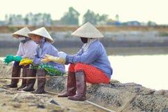 I lavoratori vietnamiti del sale delle donne stanno rilassando dopo il lavoro duro per raccogliere il sale dai giacimenti dell'es Immagini Stock