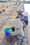 I lavoratori vietnamiti del sale delle donne stanno rilassando dopo il lavoro duro per raccogliere il sale dai giacimenti dell'es Fotografie Stock