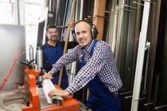 I lavori professionali che lavorano alla macchina del tornio in PVC comperano immagine stock libera da diritti